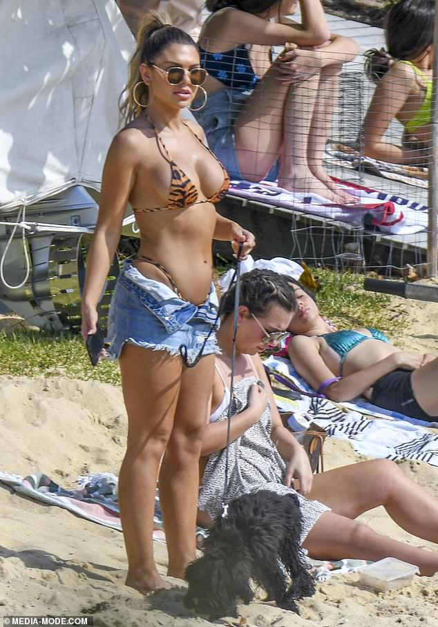 Don't slip out! Kiki risked a wardrobe malfunction as she squeezed her buxom figure into the tiger print bikini and a pair of denim shorts