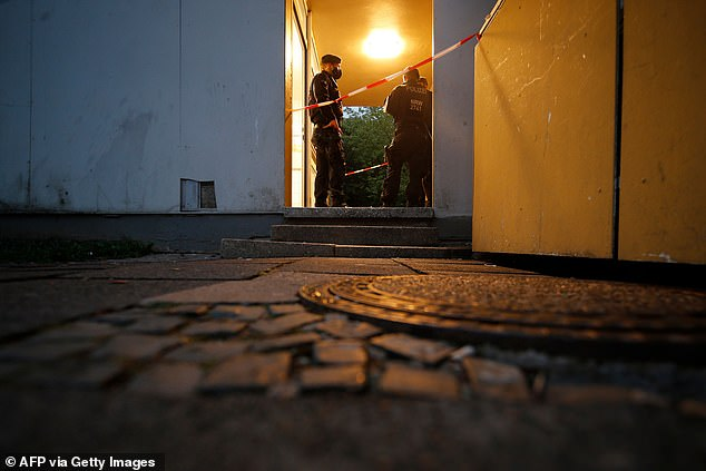 Police officers investigate the scene at the apartment complex in Solingen on Thursday evening