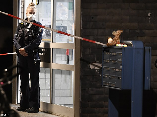 A policewoman stands in front of the apartment building in Solingen, Germany, on Thursday night