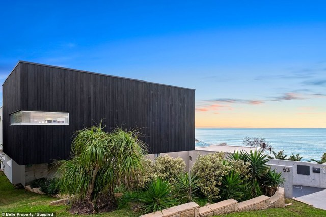 Behind the black panel walls of an unusual beach house on the New South Wales Central Coast lies a breathtaking modern family home that boasts uninterrupted views of the Pacific Ocean (exterior pictured from behind)