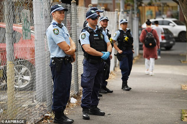 Police officers watch over activists as Extinction Rebellion staged the dirty rally in Sydney on Friday