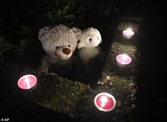 Teddy bears and candles are left out in tribute to the five children who died in what the state's interior minister called a 'family tragedy'