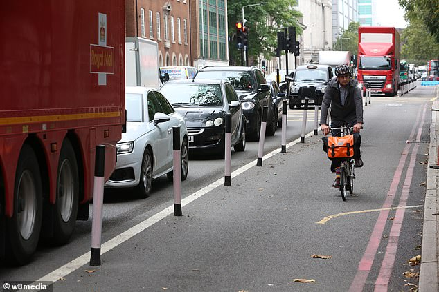 A cyclist travels down a cycle lane in London this week while cars and lorries have to queue