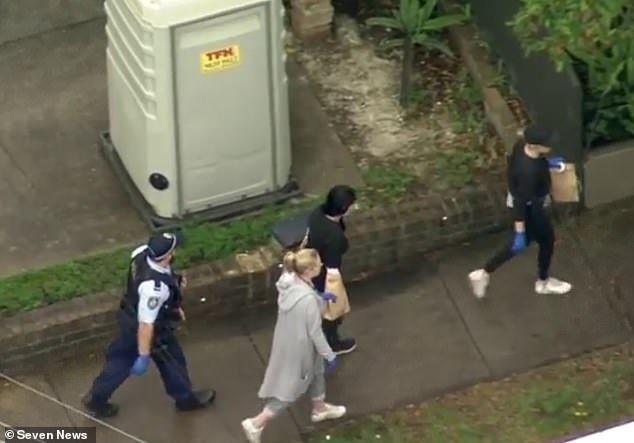 A woman (centre, right) who witnessed the shooting was led from the scene with forensic bags over her hands and taken to Newtown Police Station