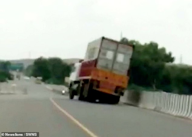 Further along the road, the lorry slips into the wrong lane again and attempts to correct its course but turns too sharply causing the back end to start lifting