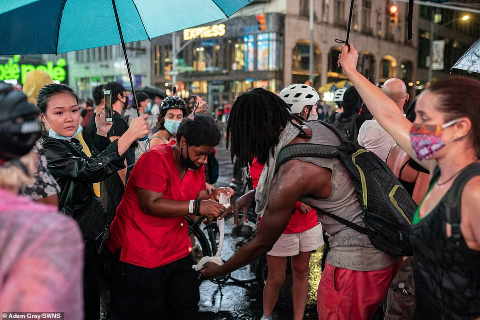 A man has his hand bandaged after a car carrying counter protestors fled the scene and drove through a crowd blocking the road during a protest for Daniel Prude and Black Lives Matter in Times Square, Manhattan, New York