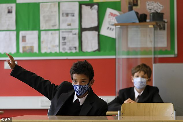 A child's risk of catching the coronavirus at school is 'extremely low', Public Health England has said, and teachers are barely at risk either. Pictured:Year seven pupils Henry Holness, left, and Eddie Favell in class during their first day at Kingsdale Foundation School in London, Thursday, September 3