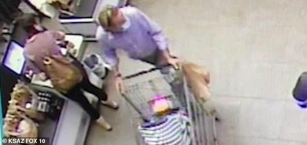 A man was caught on film trying to kidnap an infant that was inside a shopping cart while the mother (left) had her back turned toward the checkout counter at Bashas' supermarket in Flagstaff, Arizona, on Thursday morning