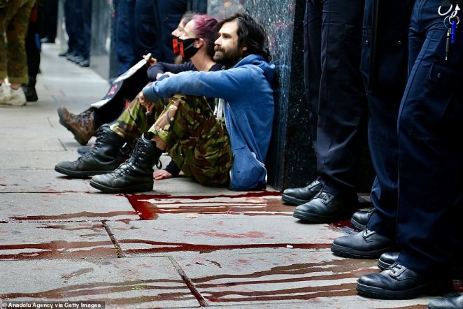 Police stand beside protesters whohave glued themselves to the pavements, which had been covered with fake blood, in a demonstration in London today