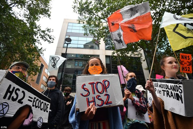 People hold signs reading 'HS2 = ecoside' and 'stop HS2'.Some 160 arrests were made on the first day of action on Tuesday, for offences including breaching public order conditions and obstructing the highway
