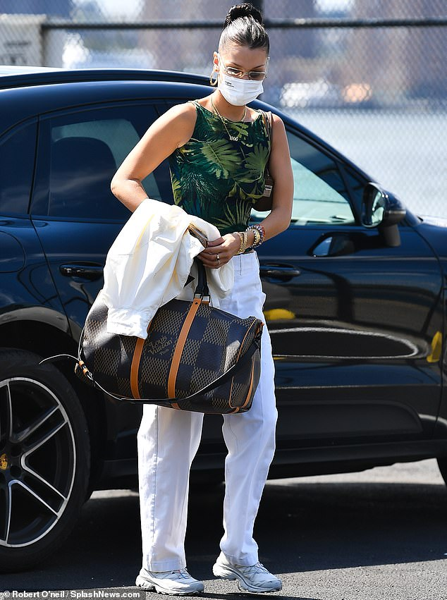 All White: Bella Hadid, 23, leaves her New York apartment as the model heads to a local helipad to embark on a weekend getaway.  The stunning brunette wore her white summer clothes as she left town with her designer gym bag in tow