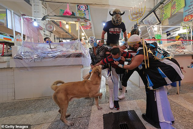 A group of Mexican wrestlers stage a playful fight with a food market customer in Mexico City as part of increasing efforts to promote the use of face masks as a preventive measure against coronavirus pandemic