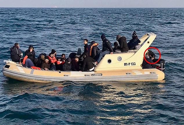 The migrant informants revealed that he was the pilot of a rigid inflatable boat (RIB) which set off from France on a calm winter¿s day last year, with 34 migrants, including women and children, bound for the Kent coast (pictured).When we scrutinised that photo, our information from the migrants was correct. A man can clearly be seen at the helm (circled) in a black jacket with the same distinctive insignia and white mark on its sleeve, as well a heavy watch on his left wrist