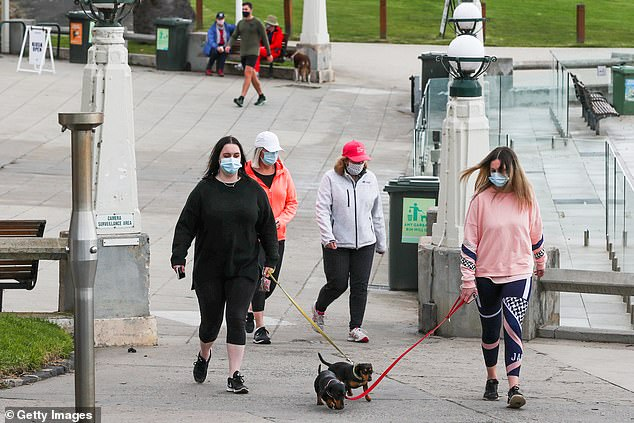 Residents in Melbourne can only exercise for one hour each day and with only one other person (pictured, residents go for a walk in Geelong on August 14)