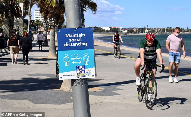 Cyclists keep 1.5 metre distance while riding along St Kilda Beach on Thursday