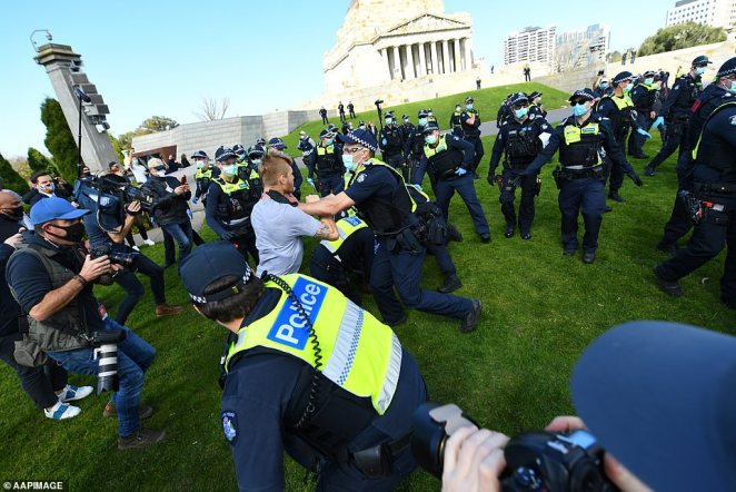 One man is seen caught in a scuffle with a Victorian police officer during the protest