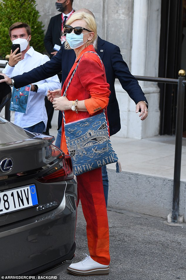 Chic style:She paired the look with a pair of white lace up dress shoes with raised platforms, and toted a blue knitted bag featuring a design picturing Venice
