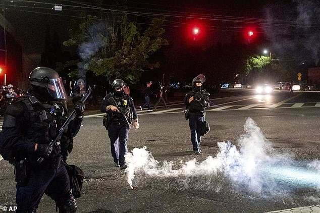 Police officers use crowd control munitions to disperse protesters