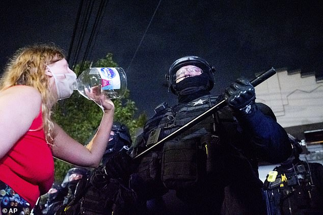 Anti-police protester Addie Mitchell yells at an officer during a demonstration
