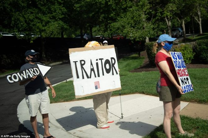 Protesters hold signs that denounce the president as a 'coward' and a 'traitor' in Sterling, Virginia, on Saturday