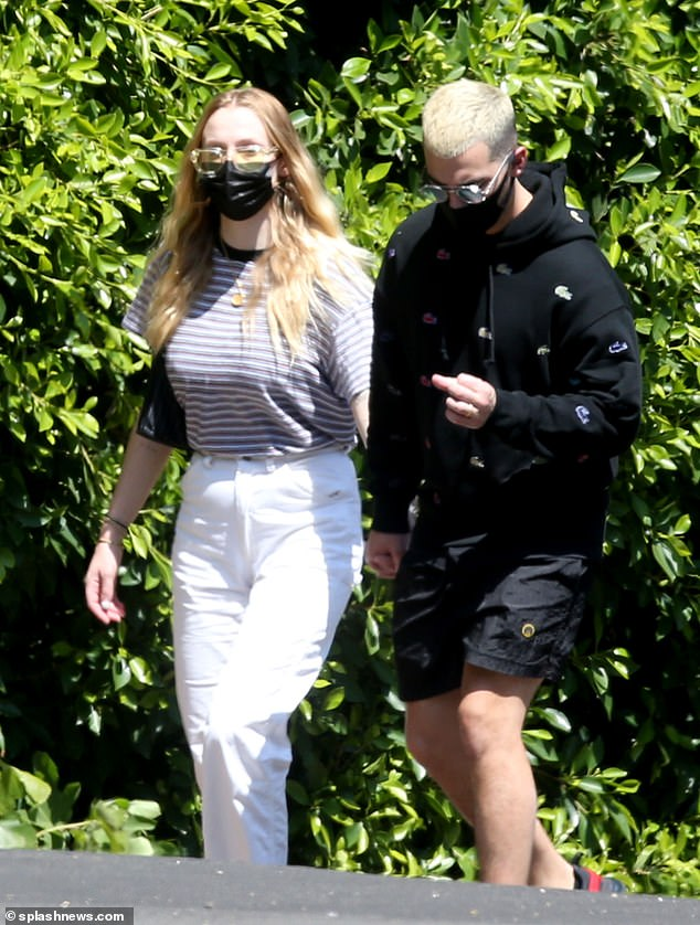 Staying Safe: She paired her look with a stylish pair of yellow-tinted sunglasses and kept her nose and mouth covered under a black mask recommended by the CDC