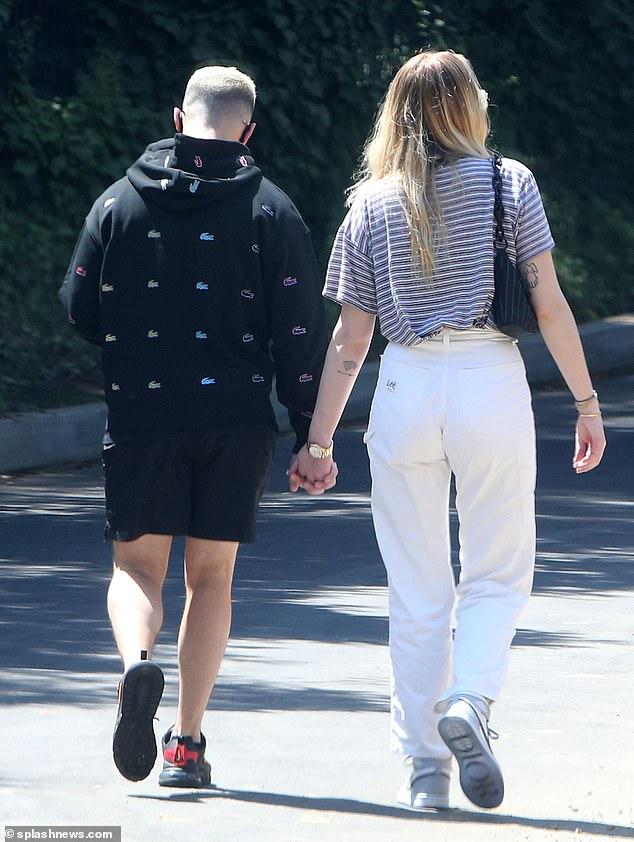 Fashion first: despite the strong Californian heat, Jonas chose to wear a chic black sweater and matching shorts