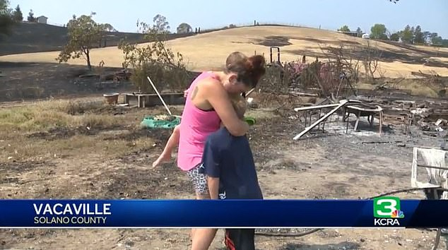 An emotional Chloe is seen holding her young sons as they survey the site where their home once stood