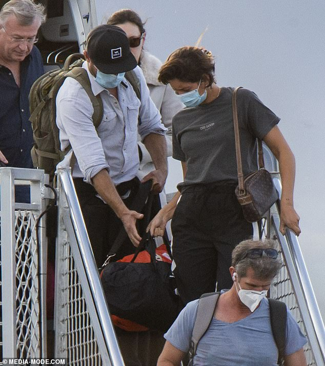 Home at last! The Hollywood hunk gladly helped the brunette carry her luggage as they disembarked the budget aircraft