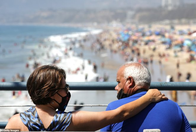 A couple is pictured on the pier in Santa Monica looking at the crowds below on Saturday