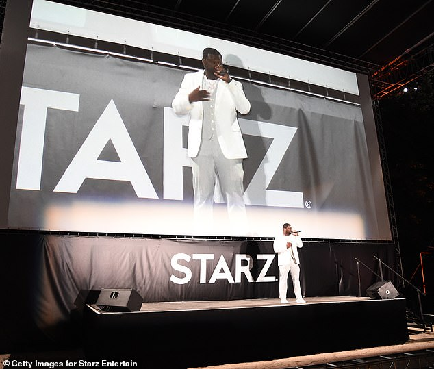 Stylish: Decked out in a white suit, the legendary rapper, 45, got on stage in front of the screen to hype up the series premiere