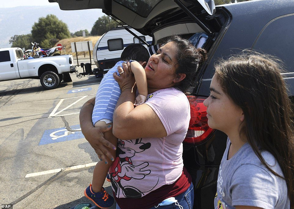 """People park their trucks as traffic comes to a stop at Highway CA-168 and Lodge Road on Saturday, the bottom of the """"four-lane,"""" as residents are evacuated near Shaver Lake"""
