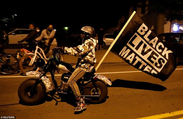 """A demonstrator rides a motorbike with a flag that reads """"Black Lives Matter"""" during a protest"""