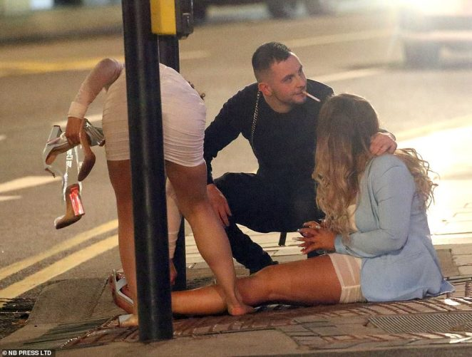 Revellers sit on the pavement as they join other party-goers for a night out in Leeds despite the city being placed on Public Health England's list of areas of concern