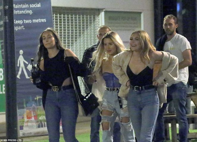 A group of people appear in high spirits at they hit the streets without face masks to enjoy a night out amid a surge in coronavirus cases