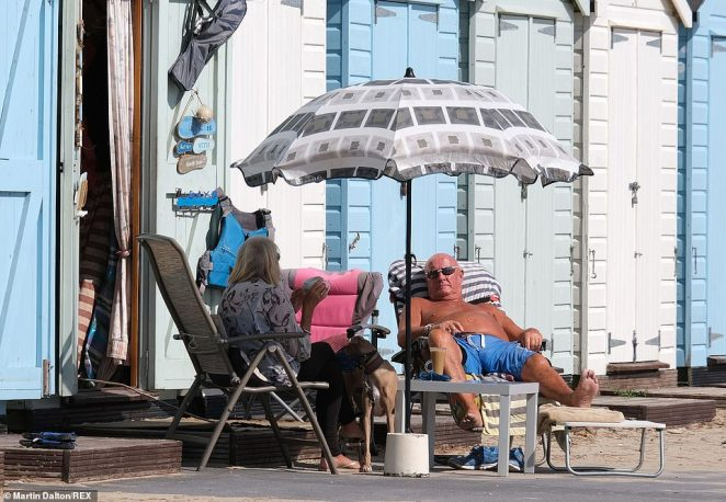 People bask in the sunshine in Mudeford, Dorset, today as showers began to slow down and leave most parts dry with clear spells