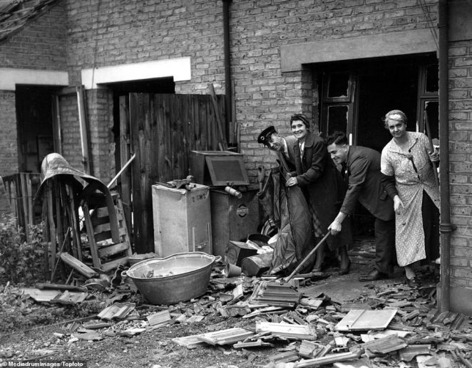 A bus driver cleans debris from an air raid up before reporting for work in Bexleyheath, Greater London. Defiant workers smile and pose for the picture despite the wreckage around them including wooden furniture, picture rails and skirting boards. A metal container is used to hold the debris. Bexley saw1,296 bombs and 11 parachute mines dropped from October 7, 1940, to June, 6, 1941