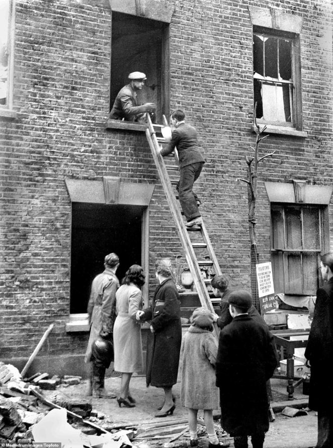 Homeowners climb a ladder to salvage some of their possessions from a bombed house in London around Christmas, after the Germans stopped bombing for three days. Manchester suffered its worse attacks during Christmas time, withThe heaviest raids occurring on the nights of December 22 and 23, 1940, killing an estimated 684 people and injuring more than 2,000