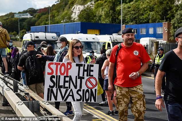 A demonstrator holds a stop the invasion banner during a protest against asylum seekers in Dover yesterday
