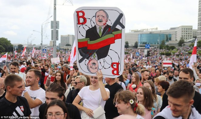 A woman holds a sign with a caricature of MrLukashenko during the rally