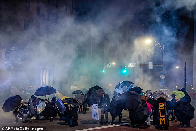 Protesters use umbrellas and homemade shields in an attempt to protect themselves from pepper,'less-lethal' munitions and teargas in Rochester, New York, on Saturday