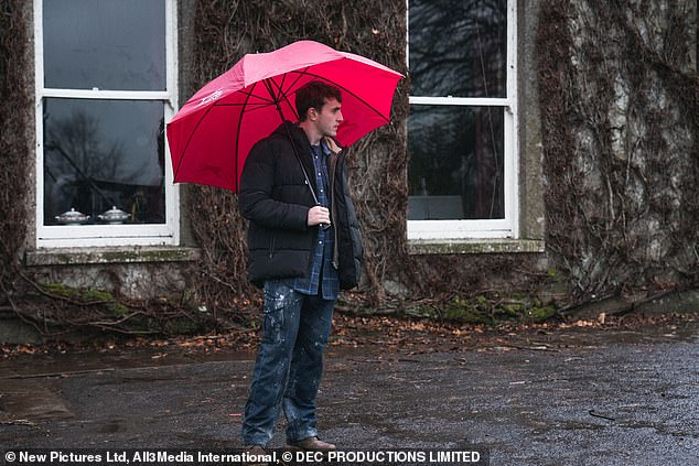 On Hold: Paul was also pictured waiting in the rain with a red umbrella while filming the series.