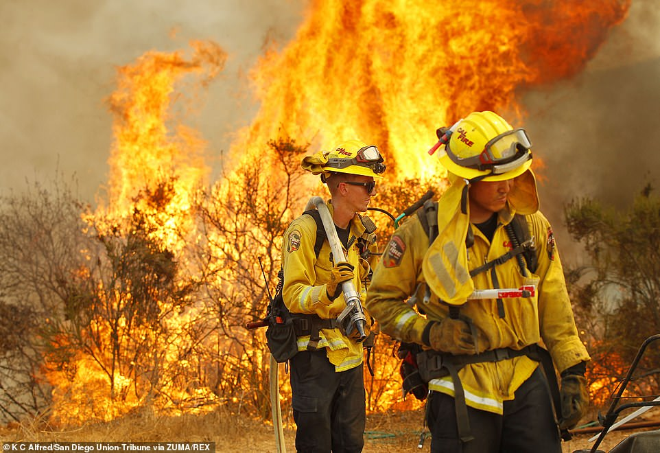 Cal Fire firefighters protect a structure near Montiel Truck Trail during the Valley Fire, in San Diego County on Sunday