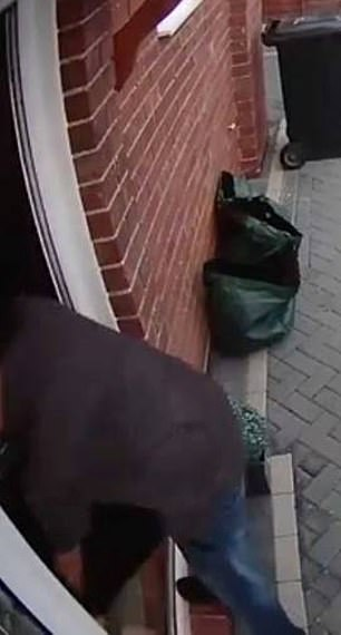 The worker leans over the doorstep to place the package inside