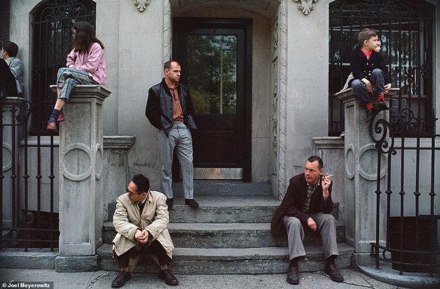 "Meyerowitz, who was born in 1938, grew up in a working-class neighborhood in the Bronx. He often spent time with his father, a salesman who sold supplies to dry cleaners and the unofficial mayor of their block. He wrote: 'My father also taught me to look at life happening in front of me. He would often whisper, ""Joel, look at that,"" or ""watch this."" And wherever he pointed, something would happen. Somebody would slip on a banana skin, or bump into a pole or stop and have a conversation with someone and then they'd wrestle each other a little.' In the above image, New York City, 1963, people watch a parade. He noted the 'muted tones' of their clothes"