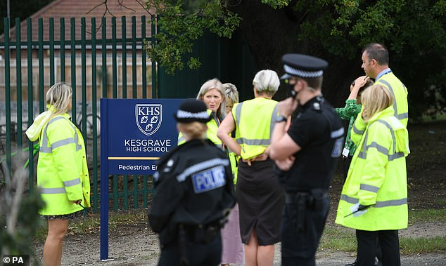 Police officers and teachers outside Kesgrave High School, the school attended by a 15-year-old boy who was shot