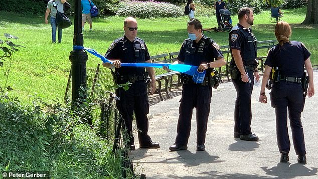 Officers pictured putting up crime scene tape near the site of the body discovery
