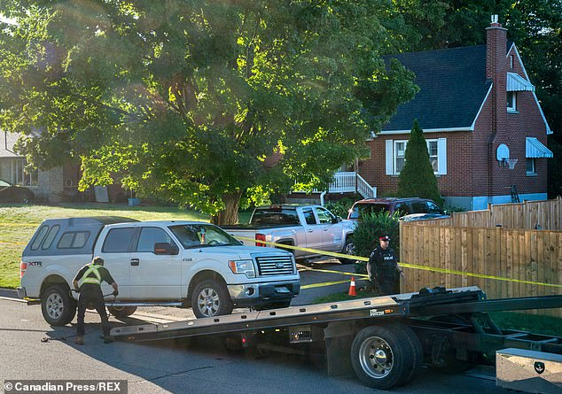 The car belonging to Lapa, which had Manitoba license plates, pictured being towed from the home Friday