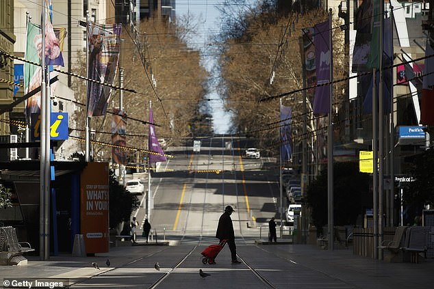 A person is seen walking across a quiet Bourke Street on September 06 amid Melbourne's strict Stage Four lockdown
