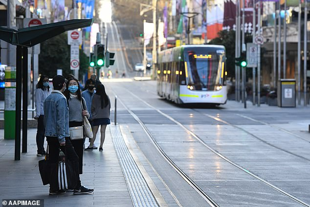 Pictured: Residents wait for a tram on Bourke Street in Melbourne on Sunday
