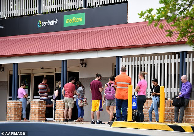 People are seen in a long queue outside a Centrelink office in Brisbane prior to the introduction of JobKeeper when the pandemic forced people out of work